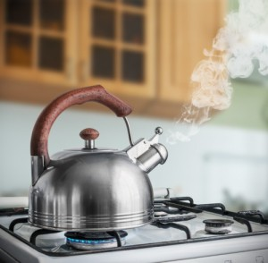 kettle boiling on a gas stove in the kitchen. Focus on a spout